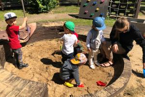 Дети в песочнице учатся делиться своими игрушками