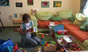 Анастасия раскладывает игрушки по коробкам