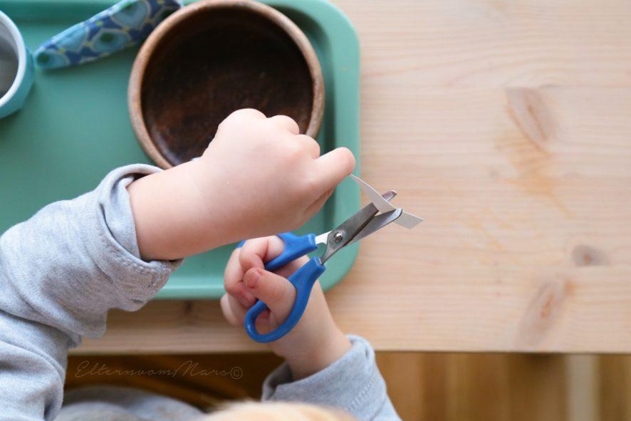 Ребёнок нарезает ножницами