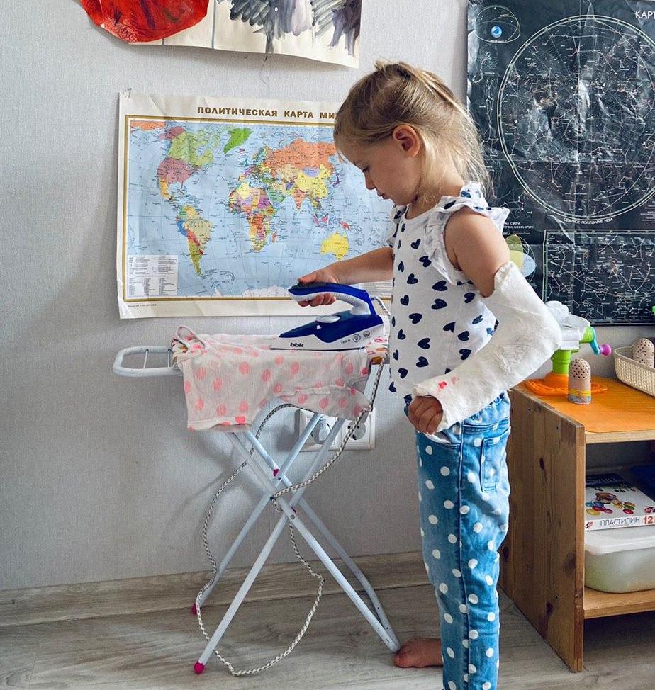 ребёнок гладит бельё маленьким утюгом на детской гладильной доске
