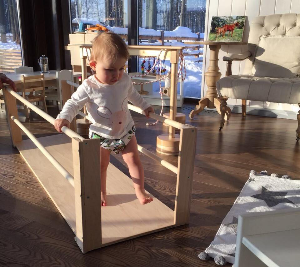 ребёнок ходит с помощью брусьев