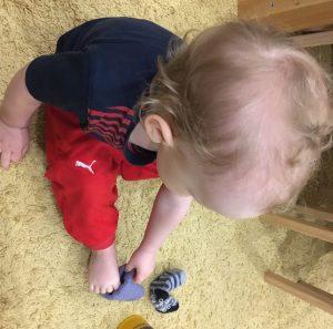 Ребёнок пытается надеть носки
