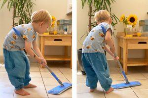 ребенок собирает шваброй пролитую воду