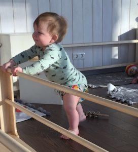 Ребёнок учится вставать с помощью перекладин