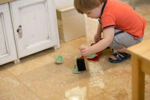 Ребёнок разбил чашку и подметает осколки