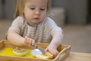 Ребёнок мажет масло на хлеб ножом