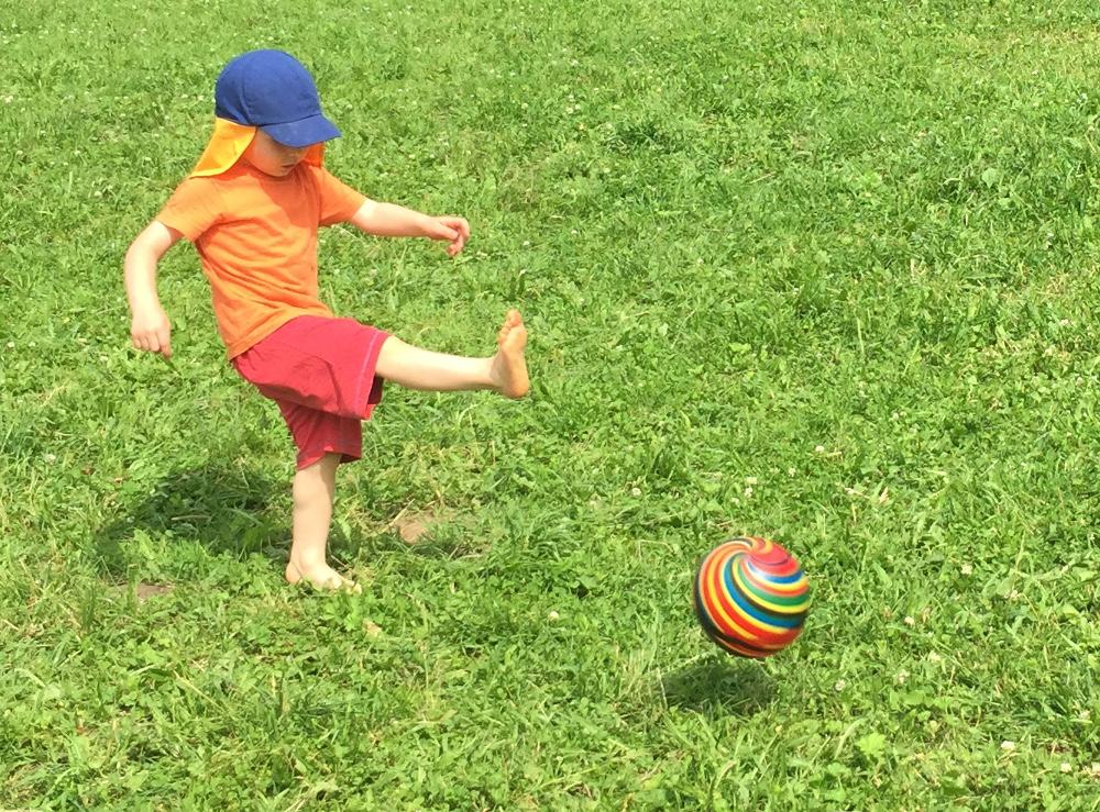 Ребёнок пинает мяч