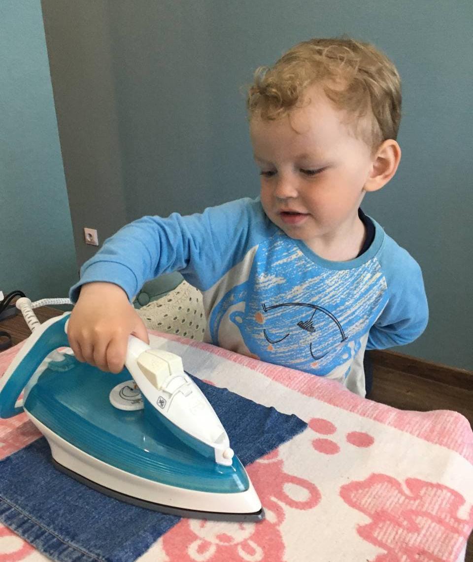 Ребёнок утюжит ткань