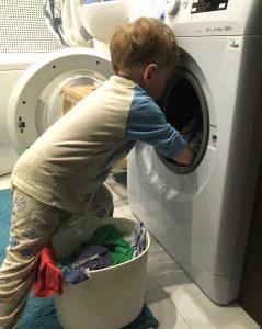 Ребёнок складывает бельё в стиральную машину